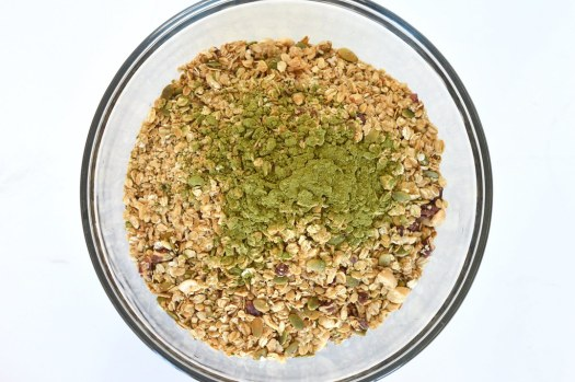 Bowl of toasted granola topped with green match powder.