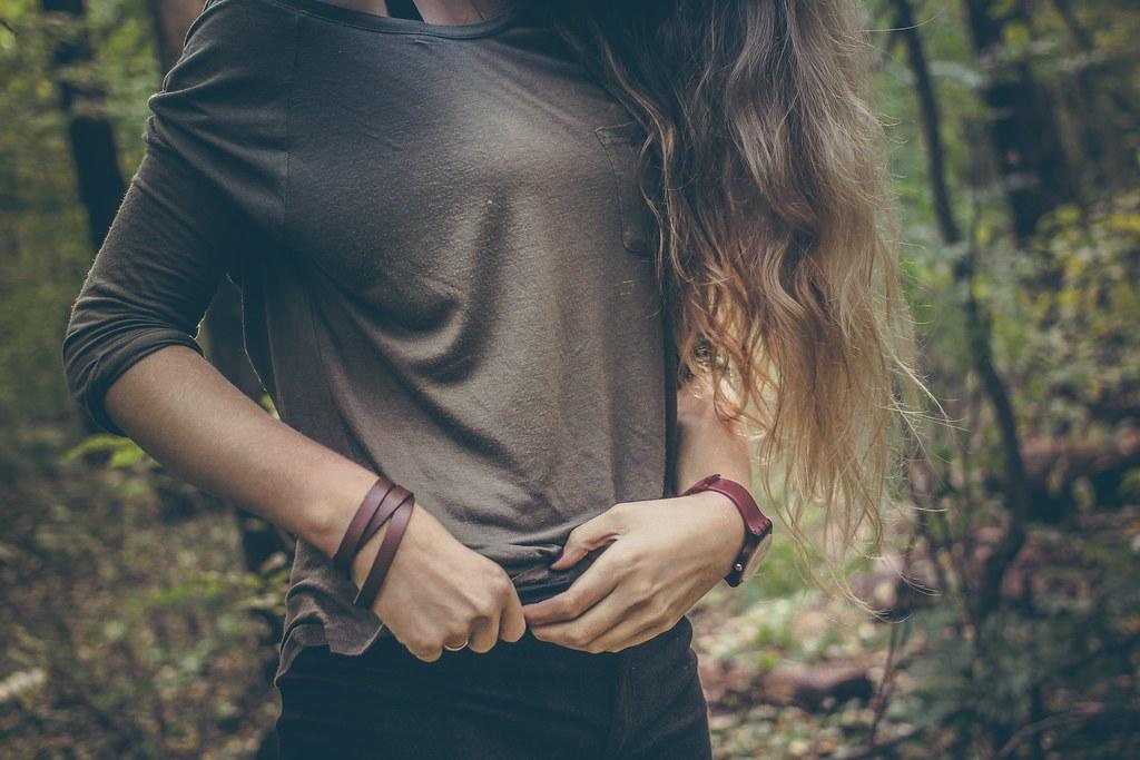 Imagen gratis de una chica en el bosque ajustándose el pantalón con las manos