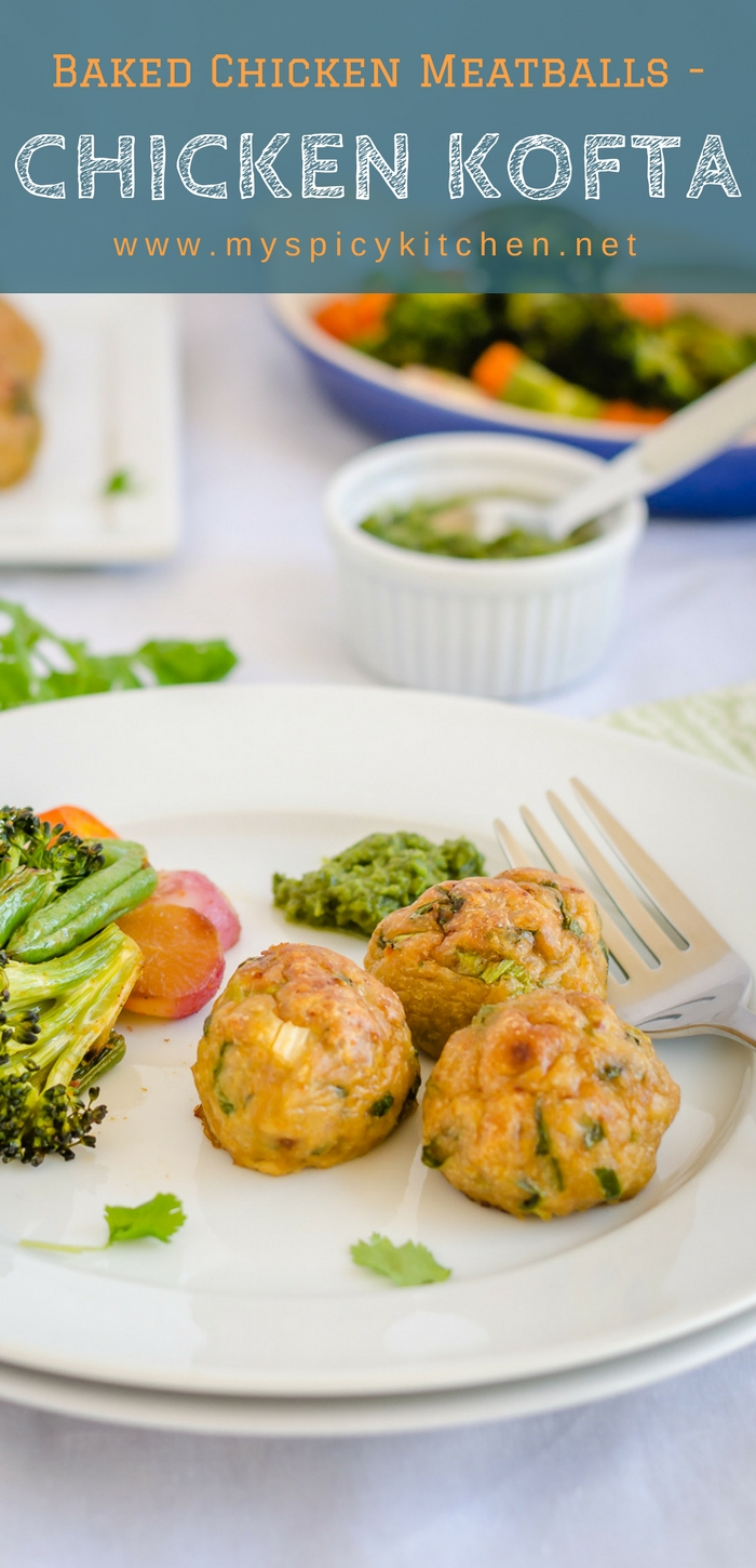 A plate of healthy, baked chicken meatballs seasoned with Indian spices and served with baked vegetables.