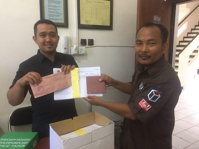 Kasubbag Program dan Data Mohammad Khoirul Anam memberikan data pemilih potensial non E-KTP kepada Dispendukcapil Tulungagung (16/3)