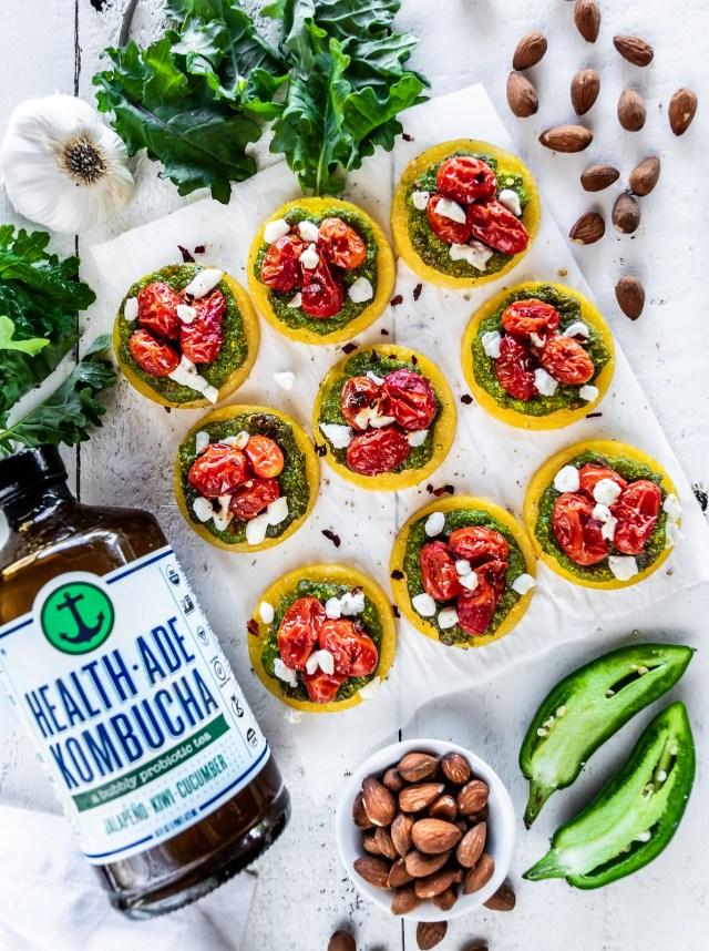 polenta mini-pizzas with kale-jalapeño pesto, burst cherry tomatoes, and goat cheese