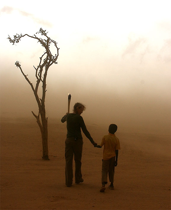 In August 2007,  At the commencement of the Dream for Darfur torch relay, Mia Farrow and an 8 year old Darfurian refugee walk into a sandstorm near the Sudan-Chad border. By the Genocide Intervention Network, used with a Creative Commons license via flickr.