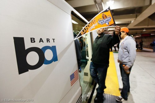 A Giants fan holds his team's banner before riding BART
