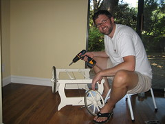 Photo of Stu holding a powerdrill and trying to assemble the bassinet