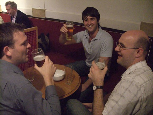 Photo of people raising beer glasses to the camera and smiling