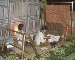 Orang menulis batik tulis dengan canting dan malam