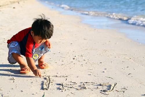 boy young beach solo alone sand beach squatting playing writing boy philippines pinoy filipino rural