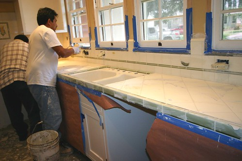 Esteban grouting the tile.