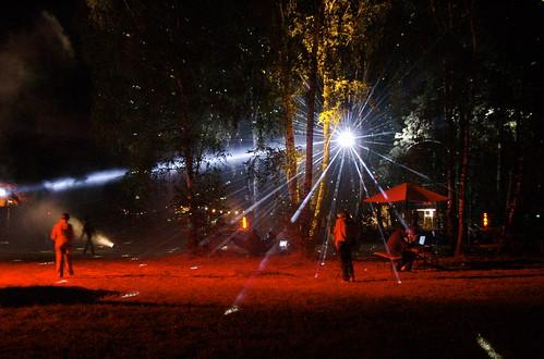 eh, questa non è facile, è una palla da discoteca (quella con tutti gli specchietti) appesa tra degli alberi e con una luce puntata. È notte e i raggi di luce si confondono tra i rami e le foglie degli alberi che la circondano.