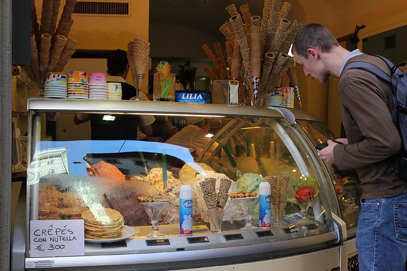 A tourist checking delicious mountains of gelato