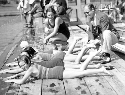 Coach Ray Daughters and swimmer Helene Madison on a dock giving swim instruction to four children
