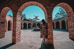 My sister standing in an archway at the Hamilton Gardens on a bright sunny day - shot with a Sony A7iii with Laowa 15mm f/2 lens