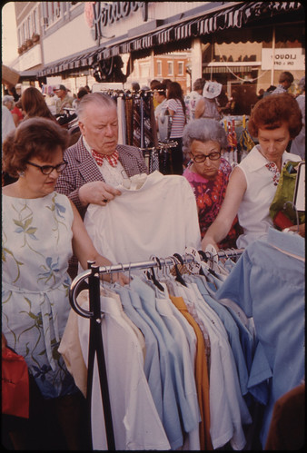 Adults Looking over Bargain Merchandise Placed in the Street on the Sidewalks by Merchants in New Ulm, Minnesota, During Their Annual Summer Crazy Days Sale. The Town Is a County Seat Trading Center of 13,000 in a Farming Area of South Central Minnesota.