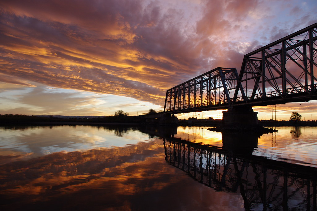 Sunset illuminates clouds with train bridge