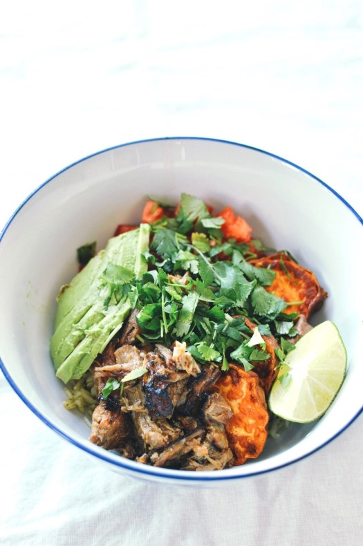 Pork carnitas burrito bowl with roasted yams, avocado, tomatoes, cilantro and lime.