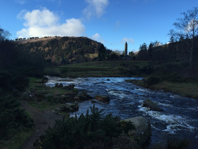 The Glendalough river with the mysterious round tower of medieval Glendalough in the background.