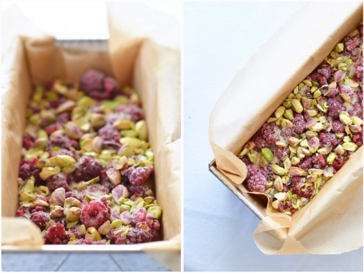 Loaf pan filled with cake batter, topped with frozen raspberries and pistachios before it is baked.