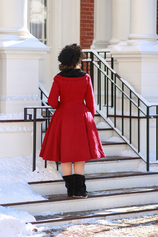 Back view of the Hell Bunny Vivien coat in red, with black hat and Royal Vintage Shoes Victoria carriage boots