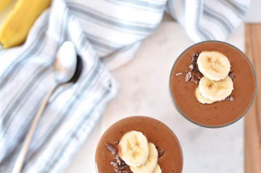 Banana chocolate smoothies topped with sliced bananas and cacao nibs