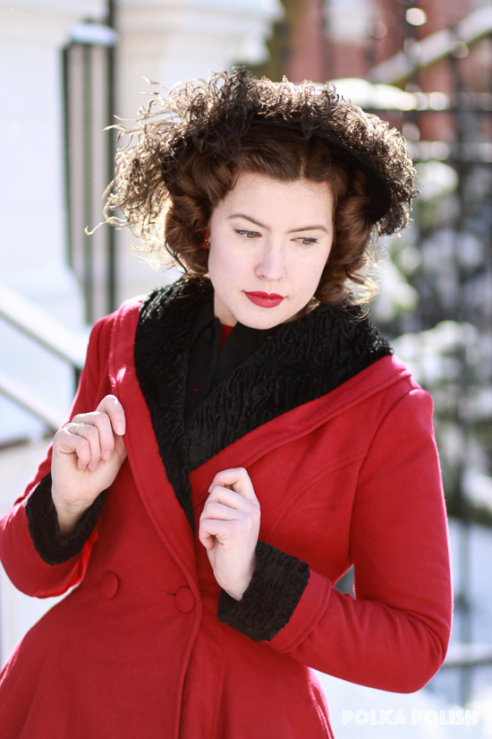 A 1950s look with a feathered hat and Hell Bunny Vivien coat on a snowy day