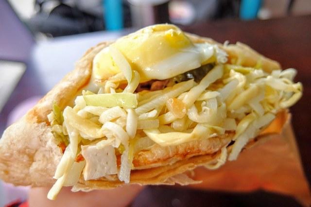 很大一份的燒餅,側面開口,裡頭塞著一顆蛋/豆干/黑輪片/榨菜等