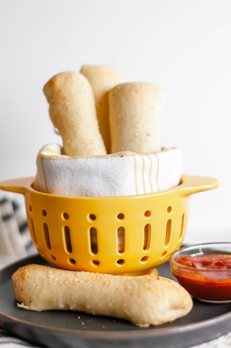 Cheese Stuffed Breadsticks are super simple, 4 ingredient perfection. Pizza dough, string cheese, butter and garlic salt are all you need for this cheesy, carb deliciousness.