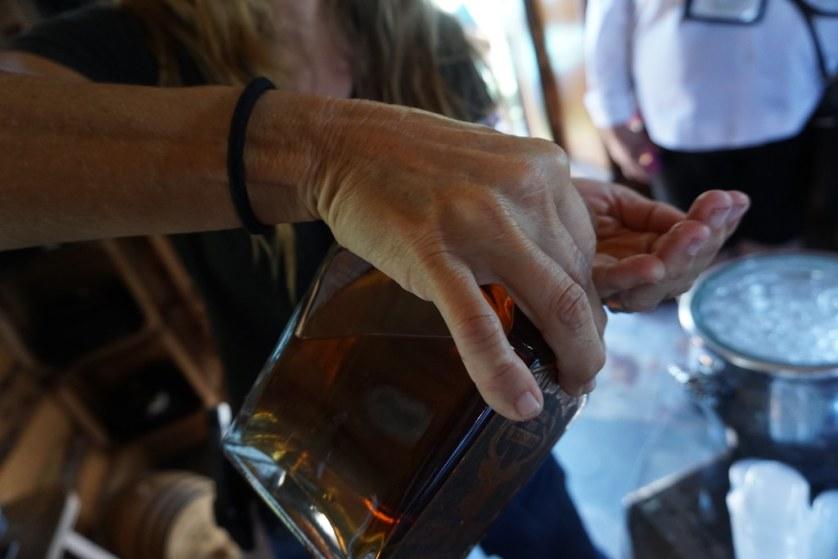 Natalie Joy Goff Pouring Wild Buck Whiskey into Her Hand at NJoy Spirit's Distillery, Brooksville, Fla, Sept. 14, 2018.