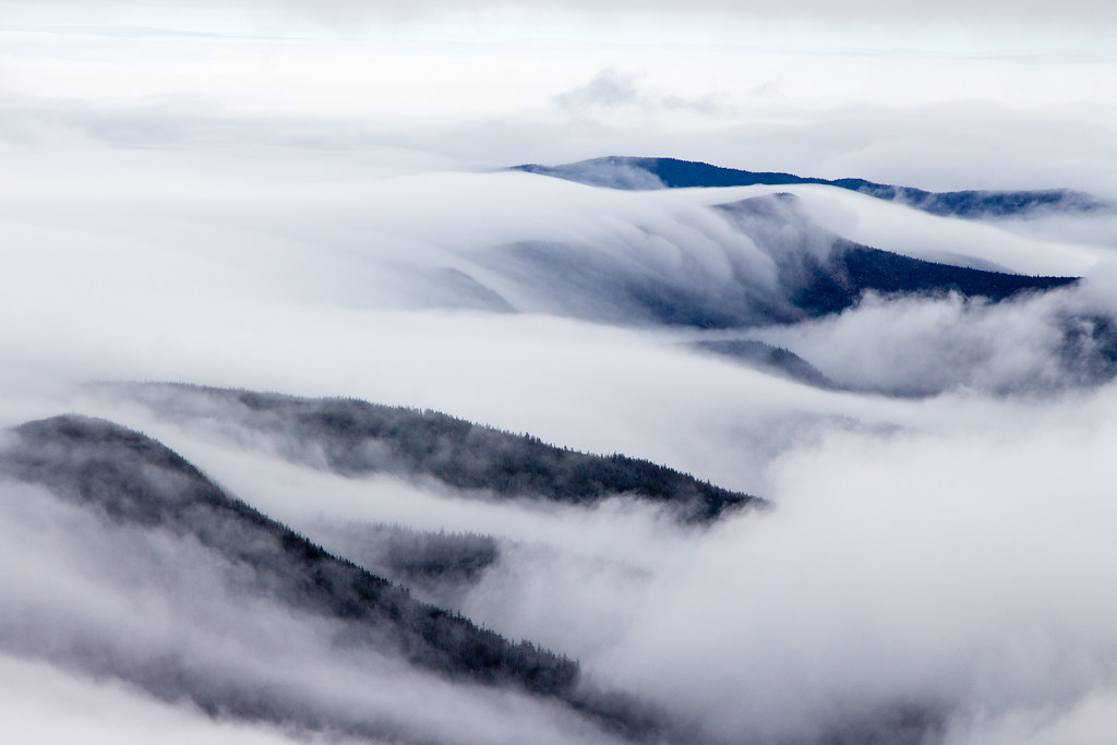 clouds rolling over mountain crests