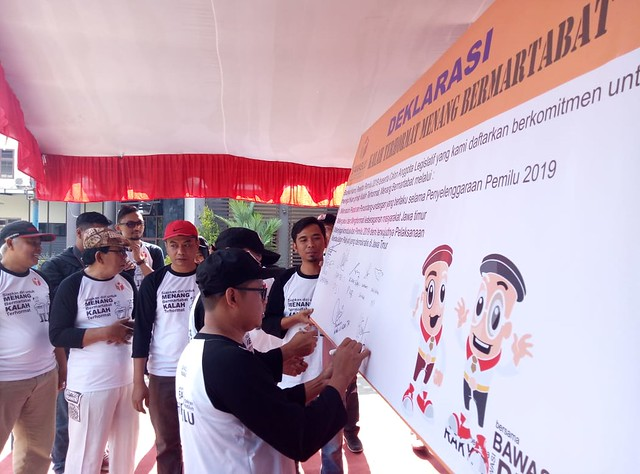 """Ketua KPU Tulungagung Suprihno, M.Pd., saat membubuhkan tandatangan pada acara deklarasi senam awas """"kalah terhormat menang bermartabat"""" di halaman gedung DPRD Tulungagung (23/9)"""