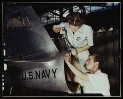 Mrs. Virginia Davis, a riveter in the assembly and repair department of the Naval air base, supervises Chas. Potter, a NYA trainee from Michigan, Corpus Christi, Texas. After eight weeks of training he will go into civil service. Should he be inducted or