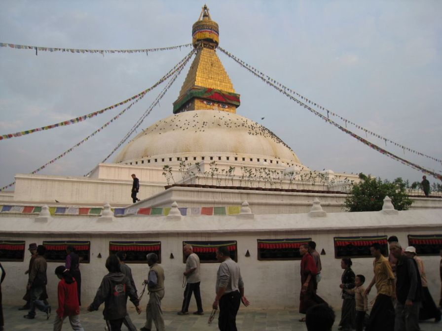 Tibetans walk clockwise around the stupa at sunset (note the malas they hold in their hands)