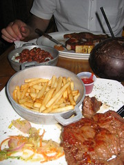 A Puerto Rican dinner with arroz con habichuleas, papas fritas, steak and piña coladas (served in a coconut)