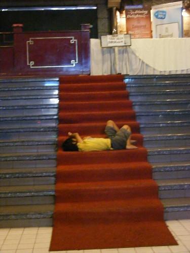 Seorang anak jalanan sedang tidur di karpet merah sebuah gedung. Lokasi: Jalan Braga, Bandung