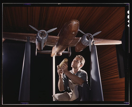 An experimental scale model of the B-25 plane is prepared for wind tunnel tests in the plant of the North American Aviation, Inc., Inglewood, Calif. The model maker holds an exact miniature reproduction of the type of bomb the plane will carry. This plant