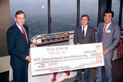 Akio Makiyama, Chairman of Maglev Transit, Inc. (right) presents a check to Governor Bob Martinez (left) and Chairman Malcolm Kirschenbaum (center right): Tallahassee, Florida