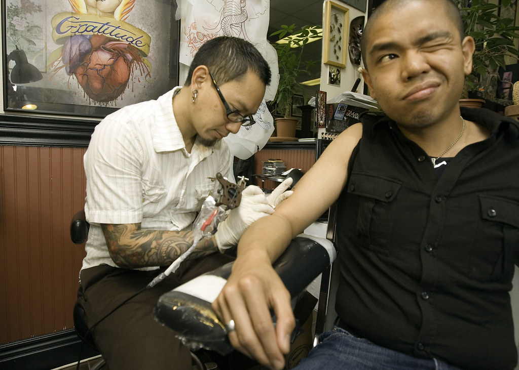 Tattoo artist, Oey from Sacred Tattoo in Oakland permanently marks my arm.