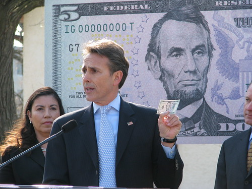 Michael Lambert, Assistant Director, Division of Reserve Bank Operations and Payment Systems, Federal Reserve Board, points out features of the new $5 bill. Anna Escobedo Cabral, Treasurer of the United States stands to the left.