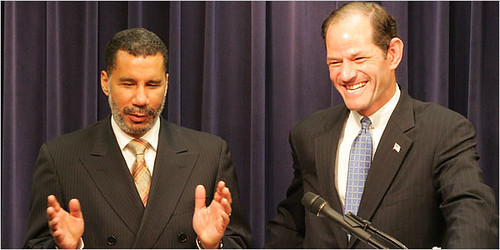 Gov. Spliter (right) laughs as he prepares to hand over the tabloids to Governor Paterson