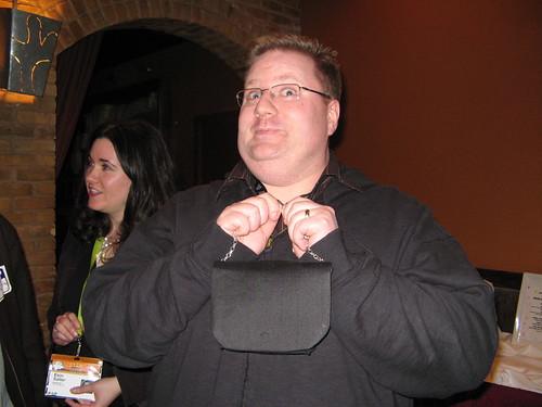 Kevin smiling and holding a tiny handbag