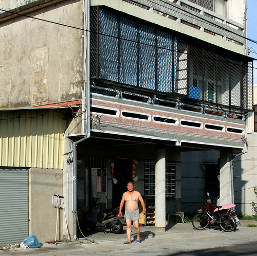 shirtless man in front of building