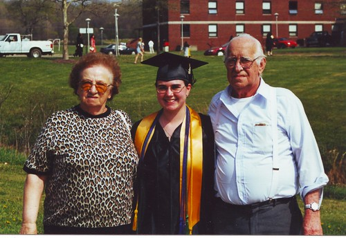 A white elderly woman with brown hair and a leopard print shirt, a white young woman in a black graduation cap and gown, and a white balding man with glasses in a button down blue shirt