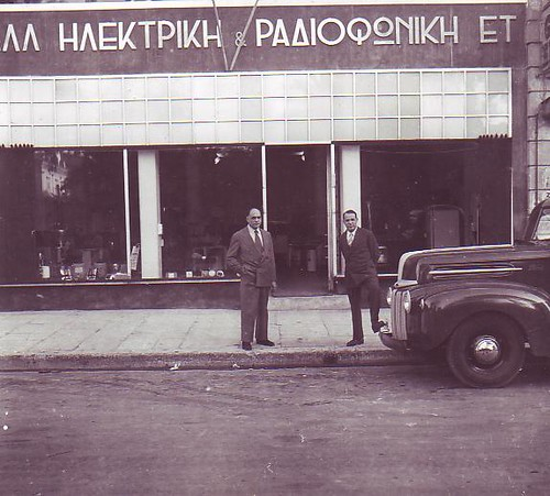 Manolis Riginos (left) and his brother George in front of the GE showroom.  The old pick-up truck was used by the company then named ELLINIKI ILEKTRIKI & RADIOPHONIKI ETAIREIA (Hellenic Electric & Radiophone Co.).