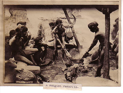 Tribesmen roast a dog over an open fire. At their feet is a severed human head -- perhaps they were celebrating a victory against an enemy tribe.   Philippine Buhay Pinoy Noon old pictures photograph black and white Philippines  Filipino Pilipino  people photos life Philippinen indigenous igorot
