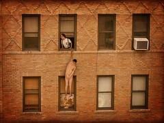 Foto de Homem nu pendurado na janela