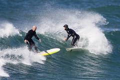 Surfers almost collide at Morro Rock, Morro Ba...