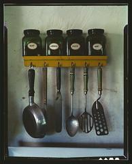 [Kitchen utensils hanging below a spice rack w...