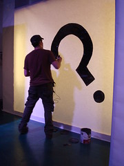 "Oscar Rodriguez paints the ""question mark"" Unpredictable logo"