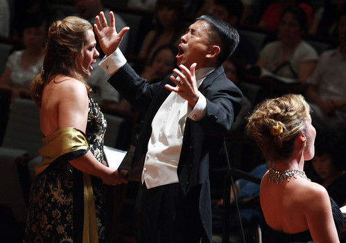 Yongyan Hu is flanked by the vocal soloists Mary Phillips, mezzo, and Heather Buck, soprano