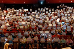 Article image: Students hold up their laptops for the camera, filling an auditorium.