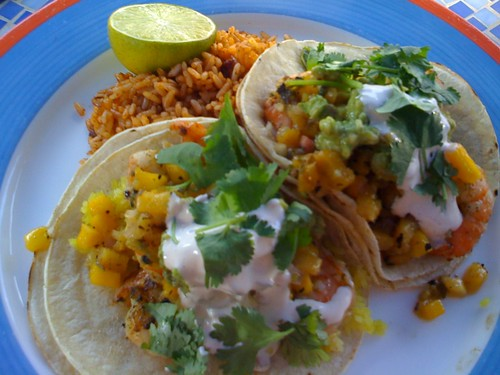 Nevis: Two grilled shrimp tacos in corn tortillas with yellow rice, pineapple jalepeno salsa, cilantro, guacamole and lime sour cream.